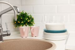 Clean dishes on counter near kitchen sink. Indoors stock photo