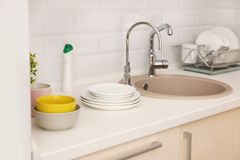 Clean dishes on counter near kitchen sink. Indoors stock photos