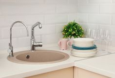 Clean dishes on counter near kitchen sink. Indoors stock image