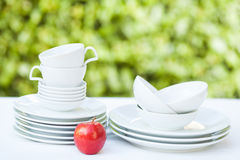 Clean dishes and cups on white tablecloth on green background Stock Images
