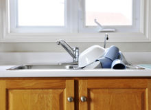 Clean dishes on kitchen sink. Pile of clean dishes on draining board of kitchen sink royalty free stock images