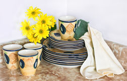 Clean dishes and yellow flowers. Clean dishes on the kitchen table with fresh flowers stock images