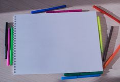 Clean drawing album with colorful felt-tip pens on the table. Clean drawing book and colored felt-tip pens are on the writing desk royalty free stock images