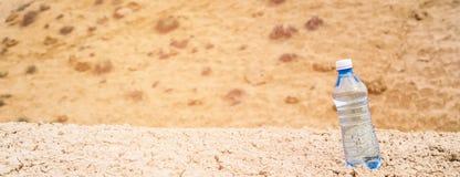 Clean drinking water in bottle in dry hot desert.  stock photo