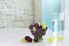 Clean drinking water in a glass, a bowl of cherries on the table. Healthy food stock photo