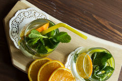 Clean drinking water with orange and mint. Cold lemonade with orange and mint in a glass. Selective focus. Top view Stock Photos
