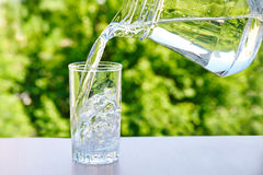 Clean drinking water is poured from a jug into a glass. On a wooden table on a green nature outdoors background