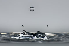 Clean drop of water splashing in clear water Royalty Free Stock Photos