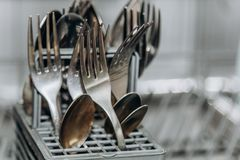 Free Clean Dry Forks And Spoons In An Open Dishwasher Closeup. Cutlery Compartment Close-up. Household Appliances In The Kitchen Stock Image - 146934881