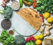 Clean eating healthy cooking ingredients with round board in center. Clean eating healthy cooking ingredients. Vegetables, beans, grains, greens, fruit, spices Royalty Free Stock Image