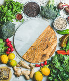 Clean eating healthy cooking ingredients with round board in center. Clean eating healthy cooking ingredients. Vegetables, beans, grains, greens, fruit, spices Royalty Free Stock Photos