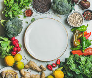Clean eating healthy cooking ingredients and round plate in center. Clean eating healthy cooking ingredients. Vegetables, beans, grains, greens, fruit, spices Stock Photos