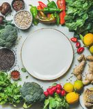 Clean eating healthy cooking ingredients and round plate in center. Clean eating healthy cooking ingredients. Vegetables, beans, grains, greens, fruit, spices Royalty Free Stock Images
