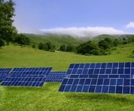 Clean electric energy solar plates in meadow. Clean electric energy solar plates generators in a green meadow Royalty Free Stock Image