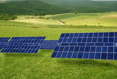 Clean electric energy solar plates in meadow. Clean electric energy solar plates generators in a green meadow Stock Photo