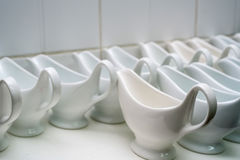 Clean empty ceramic sauce boats in restaurant. Close up empty white ceramic gravy boats in restaurant royalty free stock photography