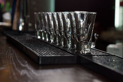 Clean empty shot glasses aligned on the bar Stock Image