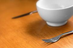 Clean, Empty White Bowl. A clean shot of a nice empty white bowl with knife and fork to the side, very shallow depth of field. Could easily be used in any deign Stock Image