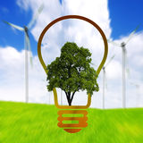 Clean energy. Bulb on wind turbines background Royalty Free Stock Images