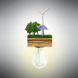 Clean energy concept The bulb is connected to a clutch of ground. With a windmill and a solar battery 3d Royalty Free Stock Photos