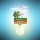 Clean energy concept The bulb is connected to a clutch of ground. With a windmill and a solar battery 3d royalty free illustration