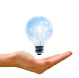 Clean Energy in our Hands. Clean energy, a light bulb with a bright sky held up by a hand Royalty Free Stock Photo