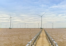 Clean energy, wind power plant with a pathway to the giant wind turbines at sea. To provide electricity for human life royalty free stock photos