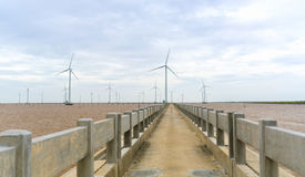 Clean energy, wind power plant with a pathway to the giant wind turbines at sea. To provide electricity for human life royalty free stock photo