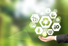 Clean environment. Hand holding signs of different green sources of energy in hexahedron shape, a 'reduce, reuse, recycle' sign in the centre. Blurred green stock photo