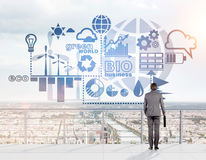 Clean environment. A man with a hand in pocket and holding a case is standing in front of a scheme of clean energy production. Back view. City view at the Royalty Free Stock Images