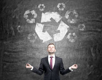 Clean environment. Man standing in front of the blackboard with hands raised as if in a posture of meditation, eyes closed. A big 'reduce, reuse, recycle' sign Royalty Free Stock Images