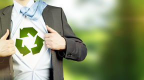 Clean environment. Man in a suit with a tie on his shoulder and shirt undone, a green sign of recyclable energy on a white background under it. No face. Concept Stock Images