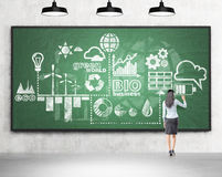 Clean environment. Woman standing in front of a green blackboard and drawing a scheme of clean energy production. Three lamps above. Back view. Concrete Stock Photo