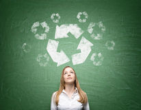 Clean environment. Woman standing in front on a green blackboard with eyes up. A big 'reduce, reuse, recycle' sign over her head. Front view. Concept of clean Royalty Free Stock Photo