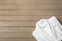 Clean folded bathrobe on wooden background. Space for text. Clean folded bathrobe on wooden background, top view. Space for text stock photography