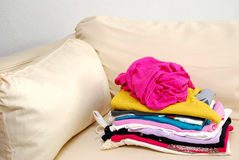Clean, folded clothes on sofa Royalty Free Stock Photography