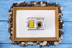 Clean frame on a blue wooden background, seashells and camera stock image