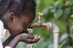 Clean Fresh Water Scarcity Symbol: Black Girl Drinking from Tap. Royalty Free Stock Photo