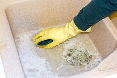 Clean a granite sink with a sponge. Housewife clean the kitchen granite sink with a sponge stock photography