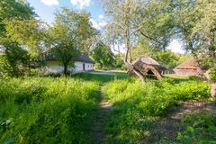 A clean and green courtyard between the old hut and the tree hill in the museum of everyday life. Uzhhorod Ukraine stock photo