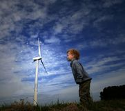Clean Green Energy. Mini giant child (3) blowing magical wind at a turbine Royalty Free Stock Images