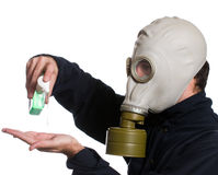 Clean Hands. Closeup view of a man wearing a gas mask using some hand sanitizer to kill any germs, isolated against a white background Royalty Free Stock Photography