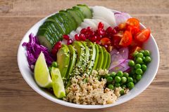 Clean healthy detox eating. Vegan and vegetarian lunch bowl. Quinoa, avocado, pomegranate, tomatoes, green peas, radish and red ca. Bbage salad royalty free stock photos