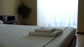 Clean hotel room after housekeeping with fragrant snow white towels on bed royalty free stock photography