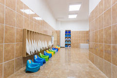Clean individual children`s potties and towels in kindergarten tile bathroom. stock image