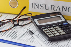 Clean insurance form, folders, pen, glasses and calculator Stock Images