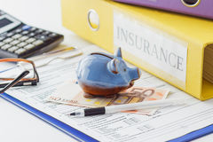 Clean insurance form, folders, pen, piggy bank and calculator. Soft focus background Stock Image