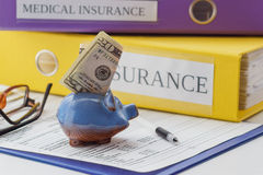 Clean insurance form, folders, pen, piggy bank and glasses. Soft focus background Stock Photos