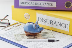 Clean insurance form, folders, pen, piggy bank and glasses. Soft focus background Stock Image