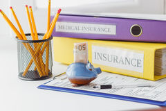 Clean insurance form, folders, pen and piggy bank. Soft focus background Royalty Free Stock Image